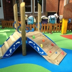 Coloured play area markings and timber climbing frame.